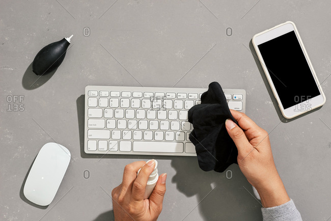 Top view close up of young man wiping keyboard with sanitizing wipes while working at desk