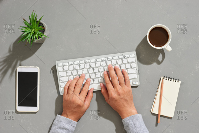Man typing on modern office desk with keyboard and other supplies with cup of coffee with copy space