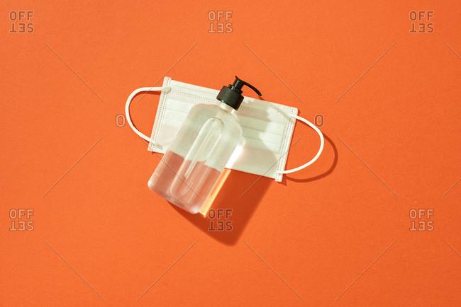 Coronavirus prevention hand sanitizer gel and protection face mask on orange background