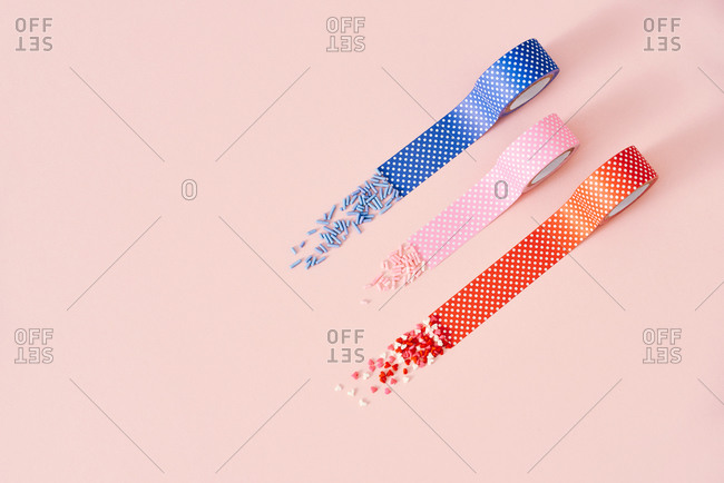 Decorative sprinkles sugar and polka dots tapes isolated on a pink background