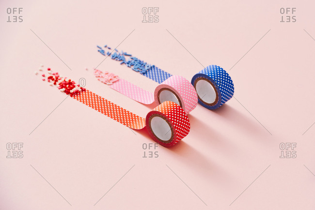 Decorative sprinkles and polka dots tapes isolated on a pink background