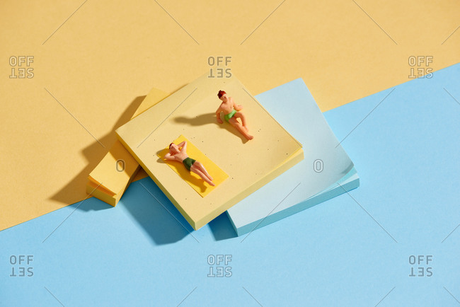 Miniature men sunbathing and relaxing on beach vacation concept