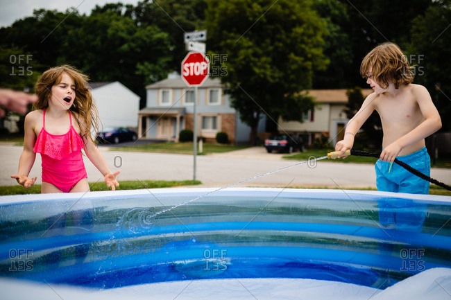 Boy spraying sister while filling up inflatable swimming pool with garden hose