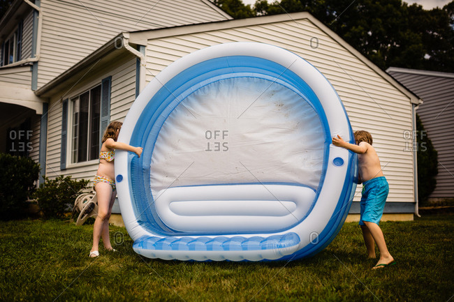 Two kids setting up an inflatable pool in their front yard