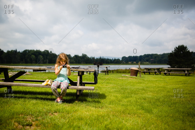 Young girl sitting on a picnic table by the lake taking pictures with a digital camera