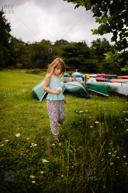 Young girl picking fresh wildflowers near a bunch of canoes