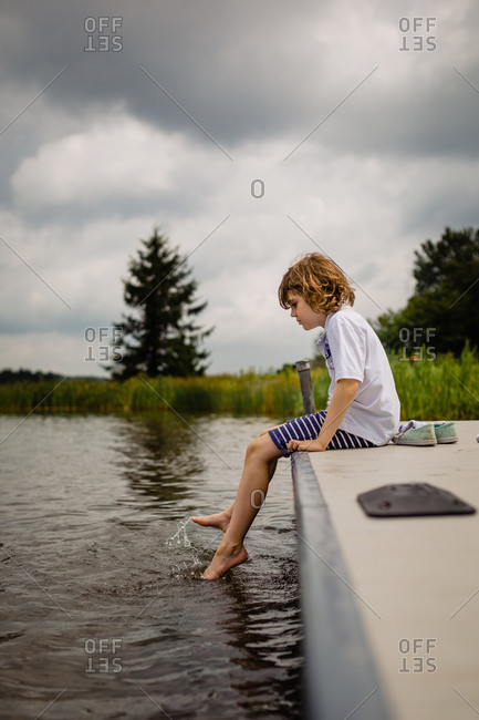 Boy dipping his toes in the lake water