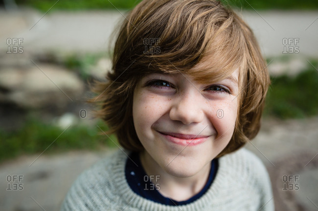 Portrait of a young boy with light brown hair and freckles smiling