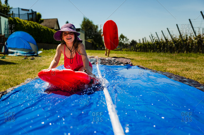 Two kids playing on a backyard water slide mat