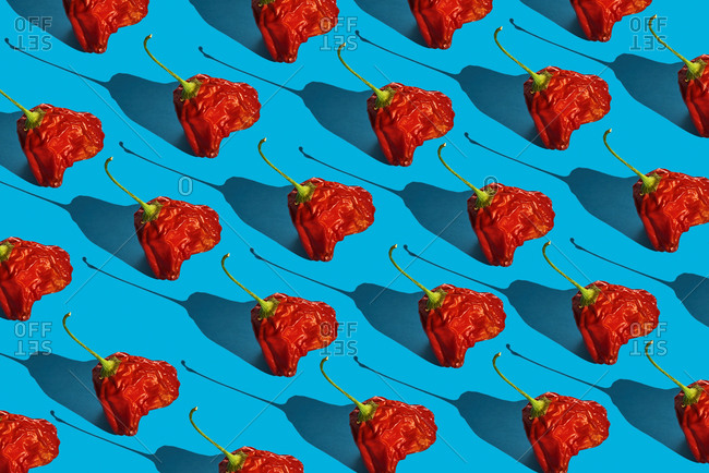A mosaic of some stale red peppers on a blue background