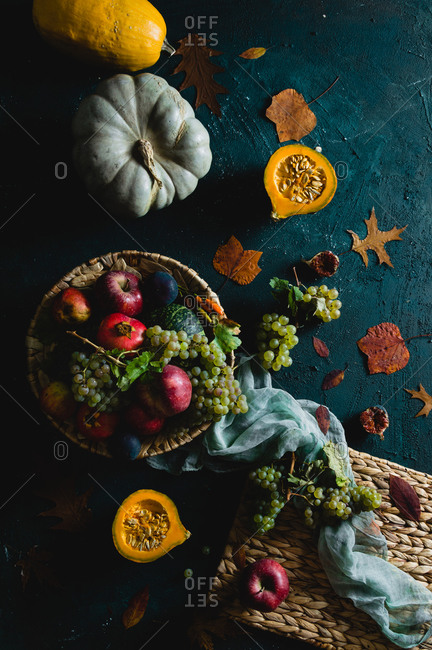 Variety of autumnal fruits in the basket with scattered leaves