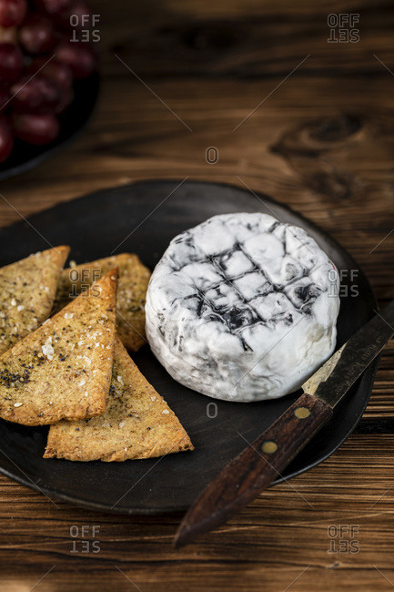 Ashed Brie served with crackers and brie on a wooden background.