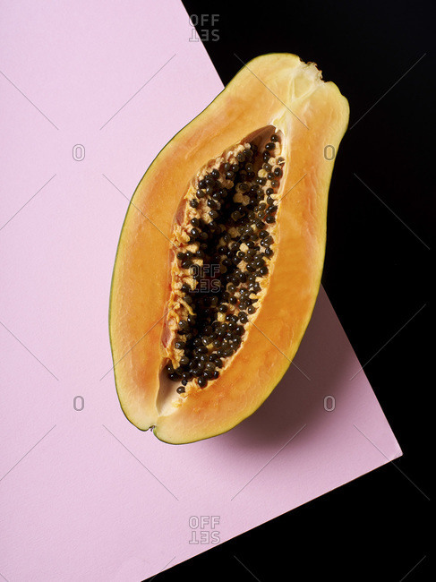 Still life composition with papaya on pink and black background.