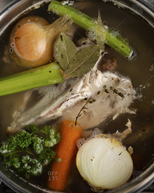 Cooking with chicken stock on the stove.