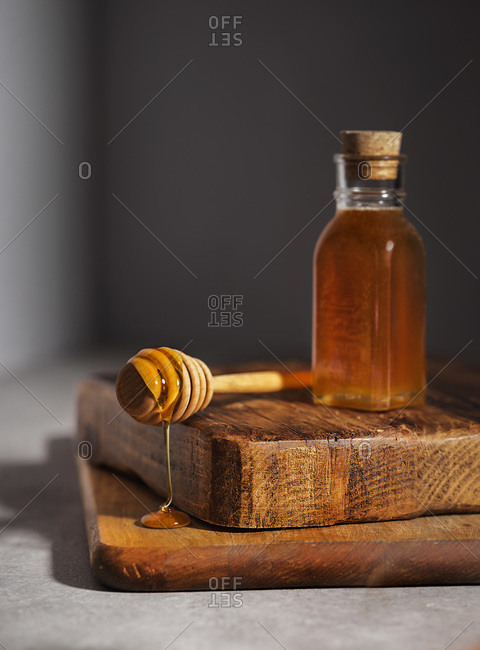 Honey dipper dripping honey onto chunky wood cutting boards against a gray wall