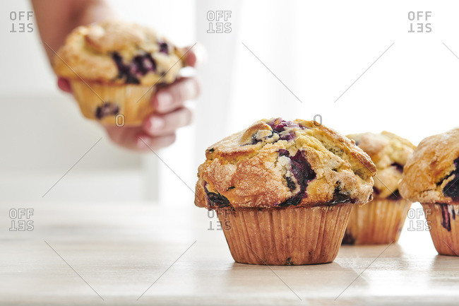 Rustic blueberry muffins on a white, wood table with bright window light in the background. A woman's hand grabs a muffin off the table in the background.