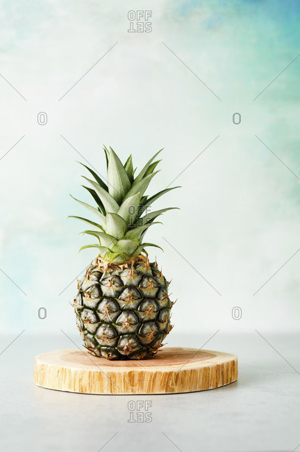 Baby pineapple on a wood board against a pale blue/green background.