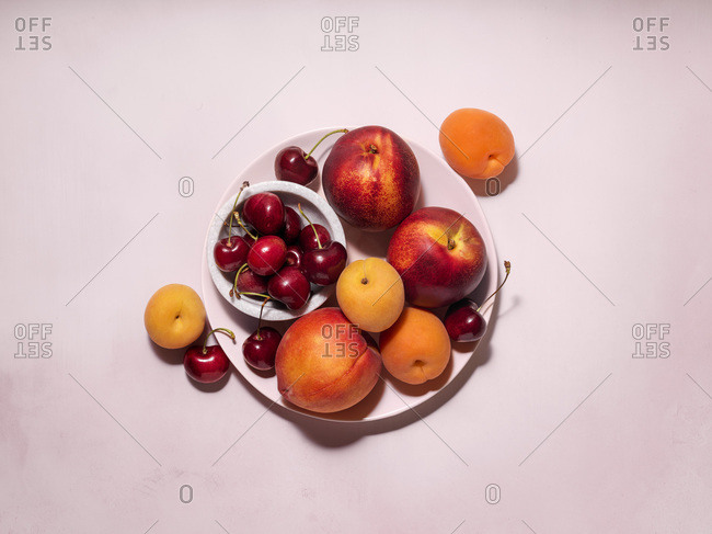 A plate filled with a variety of summer fruit (apricots, cherries, peaches, nectarines). Pale pink plate on a pale pink tabletop.