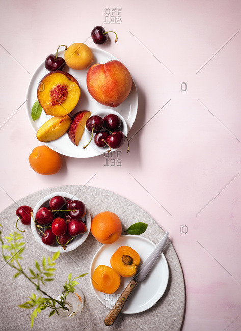 Table setting with summer fruits (nectarines, peaches, cherries and apricots). White plates on a pale pink tabletop. Bright and light.