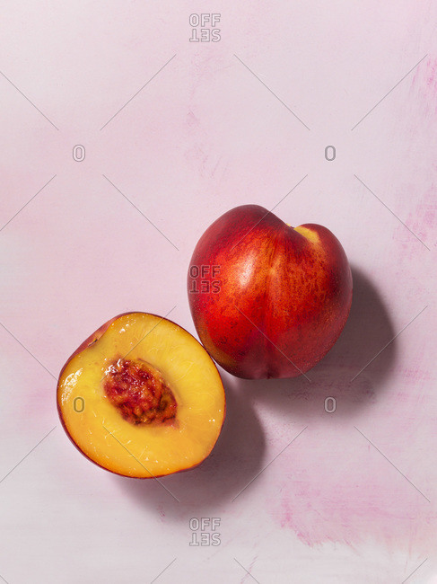 A whole and half nectarine overhead on a textured, pale pink surface.
