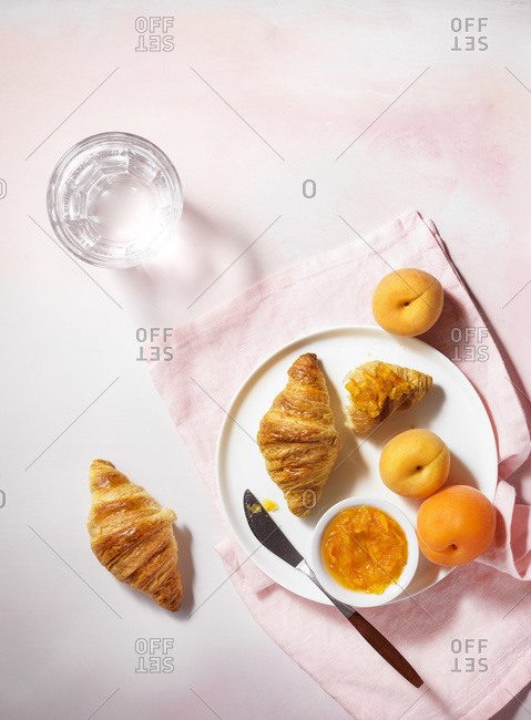 A top down view of a bright, summer breakfast scene with croissants, apricots and jam on a pale pink, textured tabletop.