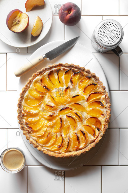 Peach tart on a plate over a white background