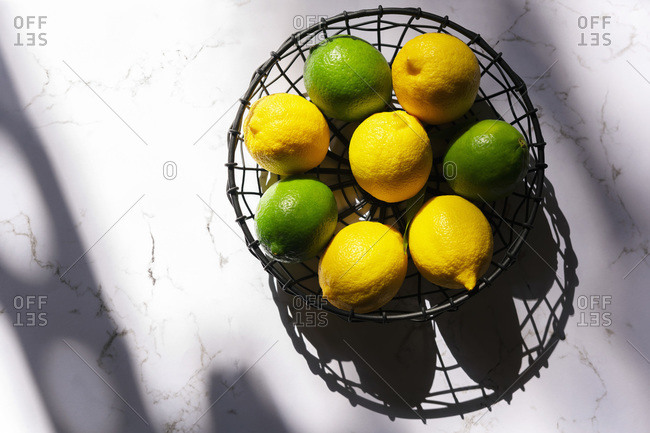 Lemons and limes in bright sunlight with shadows cast on a marbled background.
