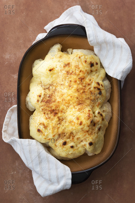 Cauliflower with cheese sauce in a baking dish.
