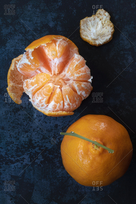 A peeled and whole mandarin on a blue background.