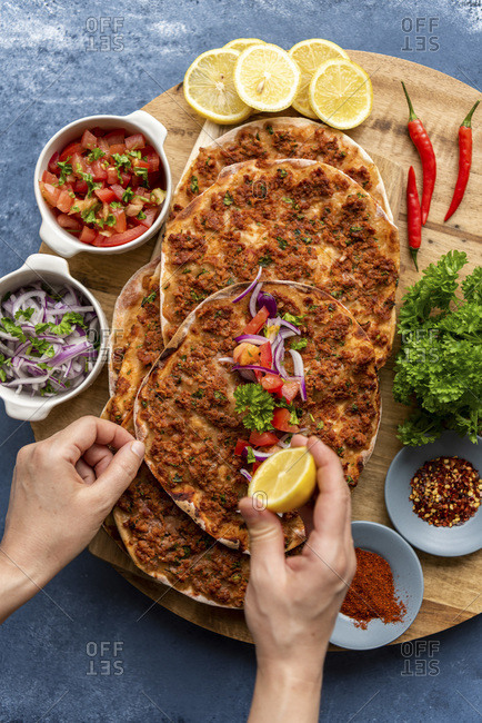 Woman squeezing lemon on a lahmacun served on a wooden board. More lahmacun portions,  red onion salad, tomato salad, chili powder, red pepper flakes, lemon slices, chili peppers and parsley accompany.