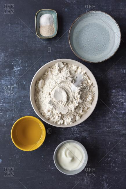 Flatbread ingredients including flour, salt, yeast, yogurt and olive oil in ceramic bowls on a dark background.