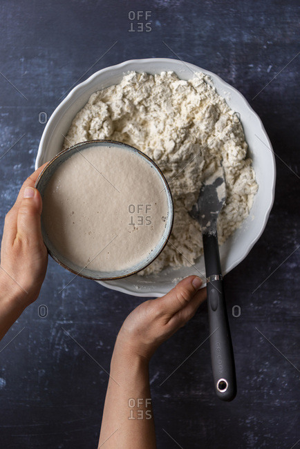 Hands pouring proven yeast into flour mixture in a large bowl on a dark background.