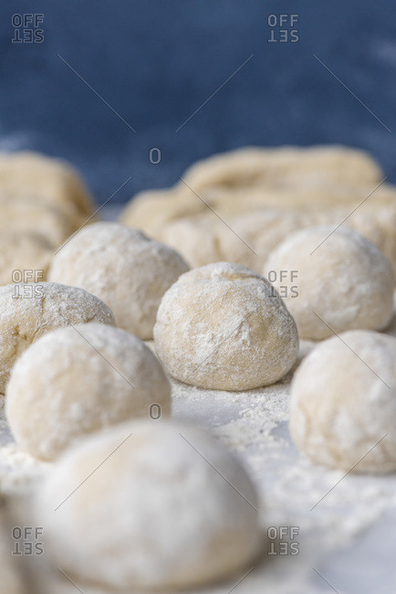 Bread dough balls slightly floured on a marble surface.