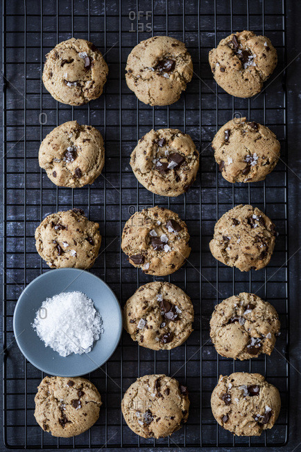 Chocolate chunk tahini cookies with Turkish coffee topped with sea salt on a cooling rack.