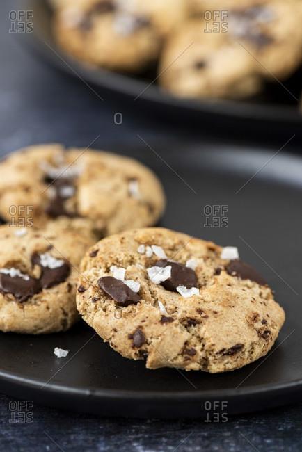Chocolate chunks tahini cookies with Turkish coffee piled on a black plate.