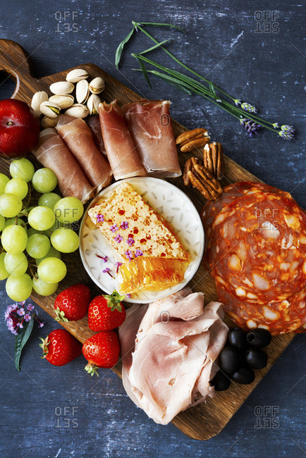 Meat platter with honey comb, chorizo, roast beef, prosciutto, grapes, pistachios, strawberries, pecans and olives on a dark background.