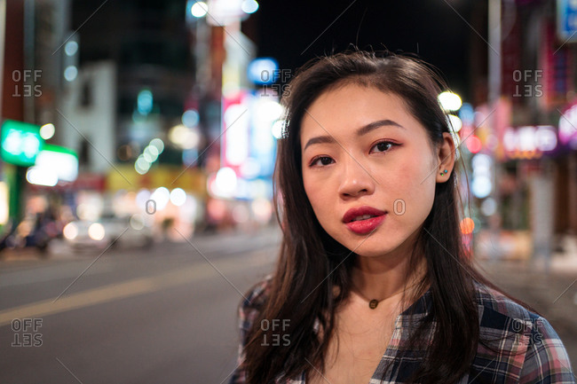 Millennial Asian female in checkered shirt looking at camera with smile while crossing street in modern illuminated city district at night time
