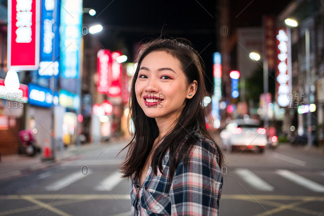 Side view of cheerful millennial Asian female in checkered shirt looking at camera with smile while crossing street in modern illuminated city district at night time