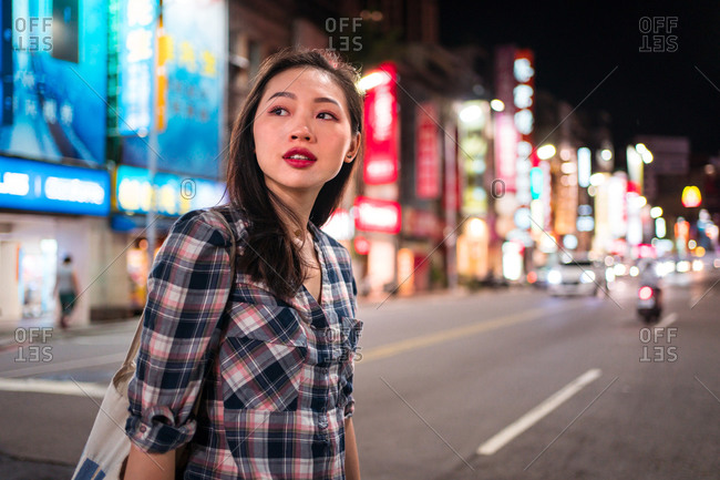 Side view of cheerful millennial Asian female in checkered shirt looking away while crossing street in modern illuminated city district at night time