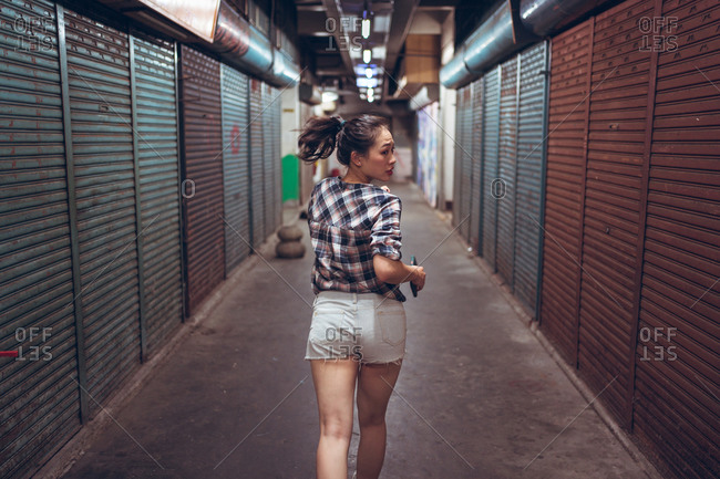 Full body young Asian female in casual clothes with smartphone in hand running fast in empty underground corridor with closed shutters