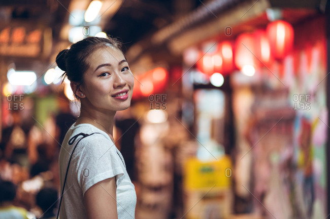 Side view of happy young Asian female in casual wear looking at camera and smiling while standing against blurred illuminated city street in night time