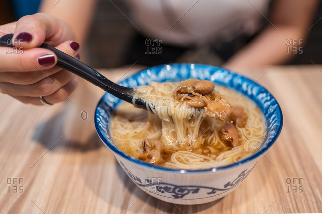 Young Asian female sitting at wooden table and eating delicious Taiwanese noodle soup in cafe