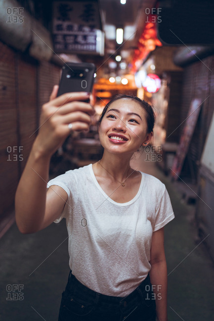 Joyful young Asian female in casual clothes taking selfie on mobile phone while standing in blurred narrow passage