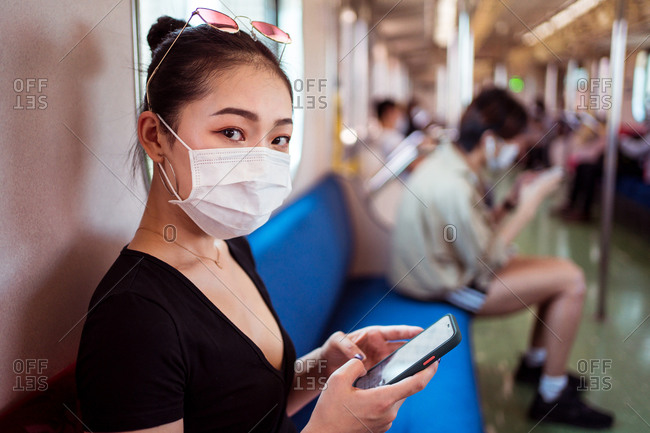 Side view of Asian female in medical mask sitting on passenger seat in train and browsing mobile phone while commuting to work during COVID 19 pandemic looking at camera