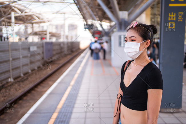 Asian female traveler in surgical mask standing on platform at railway station and waiting for train during COVID 19 epidemic