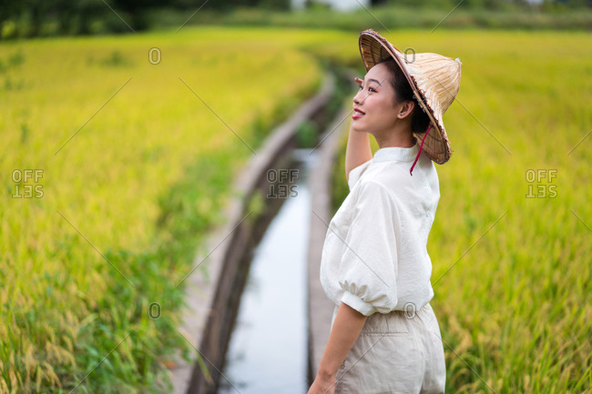 Side view of Asian female in cone hat contemplating rice field in countryside in summer