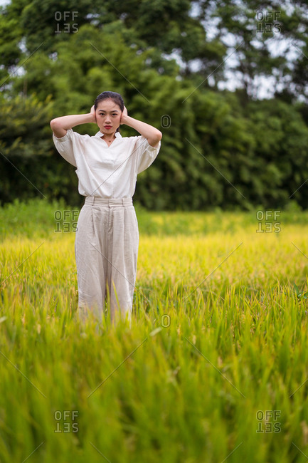 Calm Asian female standing in rice field and covering ears with hands from irritating noise while looking at camera