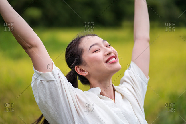 Cheerful Asian female standing in rice field with raised arms and closed eyes while enjoying freedom in summer
