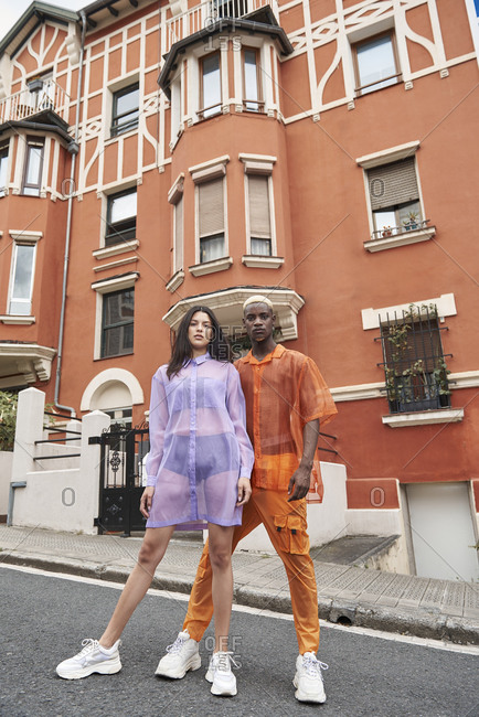 Multiethnic couple of models wearing transparent stylish clothes standing on street together and looking at camera