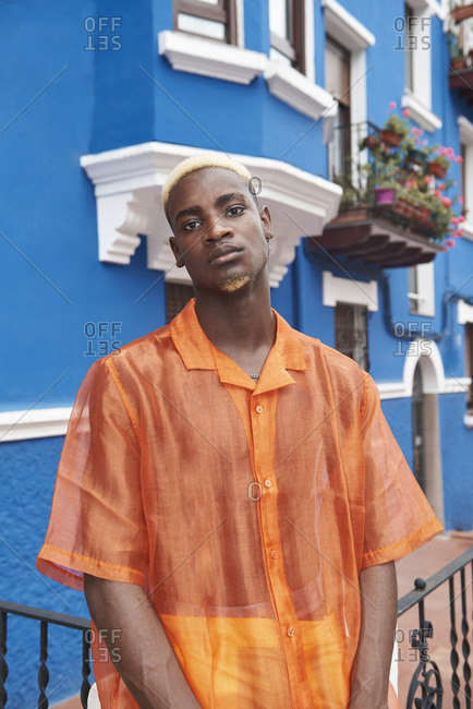 From below of young African American male in vibrant trendy clothes standing on colorful building looking at camera